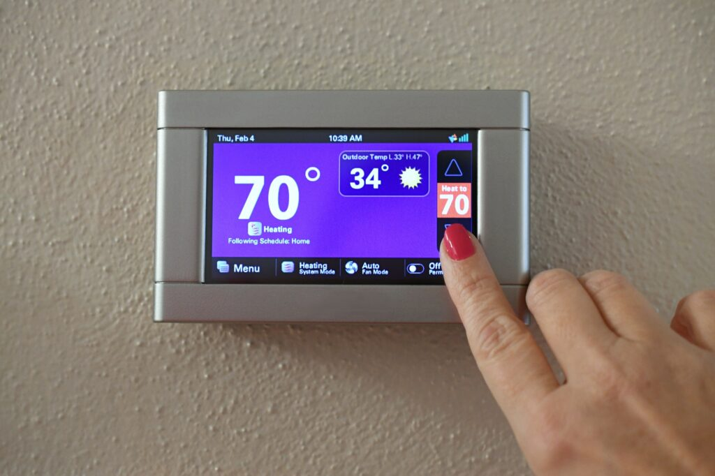 Female adjusting modern digital thermostat control pad in home to set heating cooling temperatures.