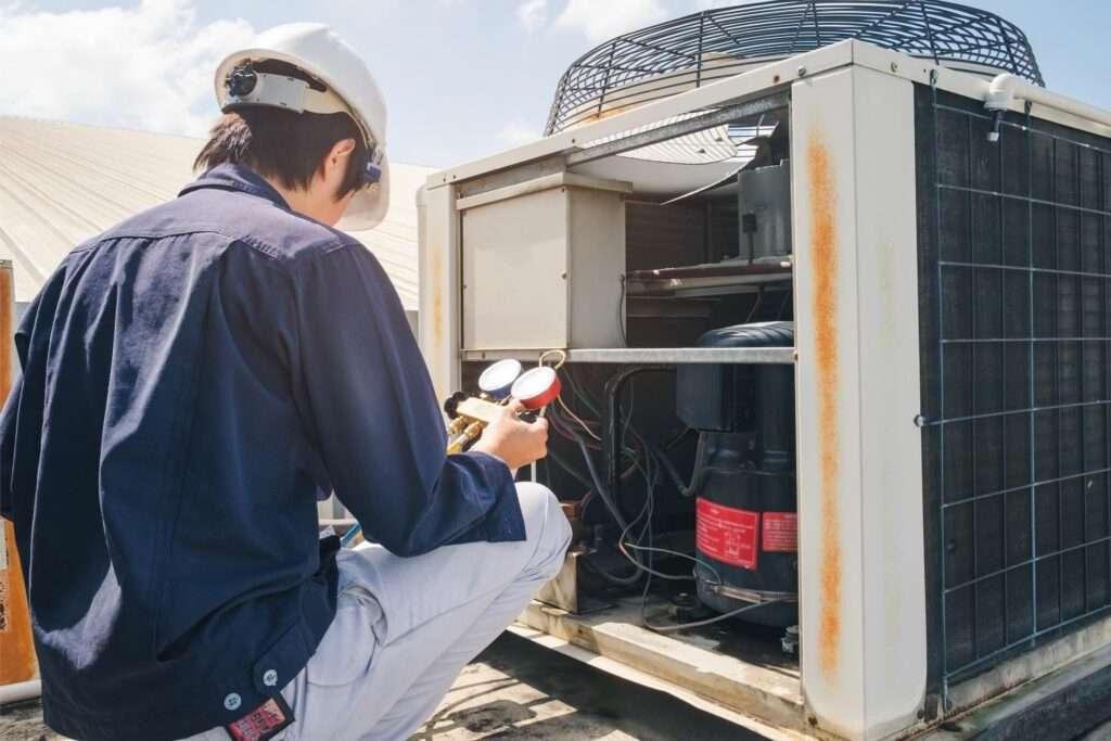 tech repairing air conditioner
