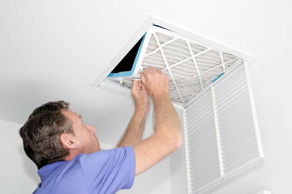 man removing filter to do HVAC maintenance