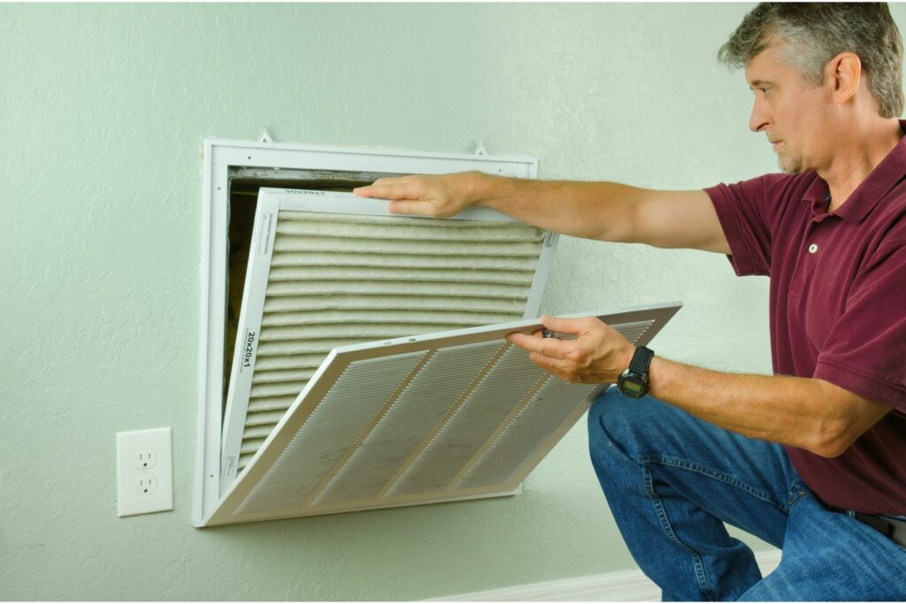 man looking into HVAC system