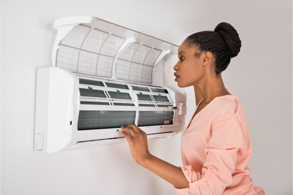 Woman checking out why AC is not working as it should